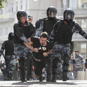 Rysk demonstrant gripen under demonstration i Moskva.