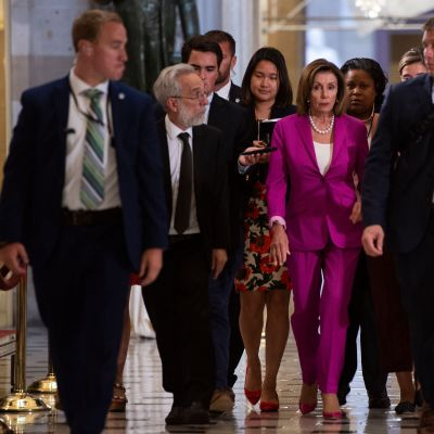 Representanthusets demokratiska majoritetsledare Nancy Pelosi omgiven av reportrar strax före omröstningen om resolutionen mot Trump.