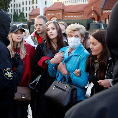 Mustissa asuisssa olevat poliisit ympäröivät naisia, jotka pitävät toisiaan kädestä kiinni. Naisten takana seisoo yksi mies.