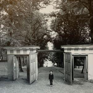 Symmetrinen kuva Helsingin observatorion avatuista porteista, joiden edessä mukulakiveyksellä seisoo poika tummassa puvussa.