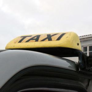 En gul, sliten taxiskylt på taket av en bil.