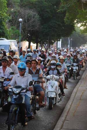 Många mopeder och motorcyklar trängs på den lilla gatan.