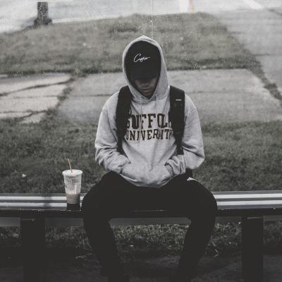 En ung kille sitter på en bänk.