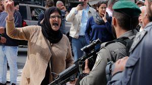 Arg palestinsk kvinna hötter med näven åt beväpnad israelisk soldat.