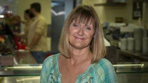 En medelålders kvinna med blont går och blå tröja står i en butik. I händerna håller hon en kaffekopp.