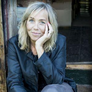 Författaren Sara Kadefors poserar på farstutrappa till liten trästuga.