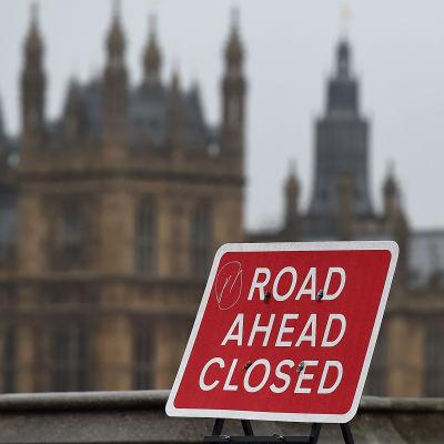 """Vägskylt """"Vägen stängd"""" med brittiska parlamentet i bakgrunden."""