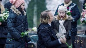 Bergdahlin perhe ja muita läheisiä haudan äärellä kukkia käsissään.