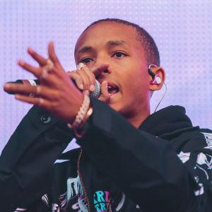 Räppäri Jaden Smith vaalean lilan screenin edessä Blockfest-lavalla. Nuori mies on pukeutunut mustaan huppariin ja hänen sormuksia täynnä oleva kätensä on edessä kuin osoittamassa jotakin.