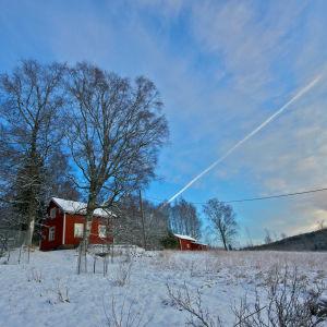 Punainen mökki talvisessa maisemassa