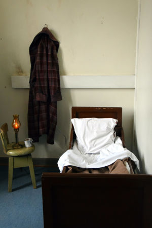 En säng, en gammal stol med oljelampa på, en morgonrock hänger på väggen.