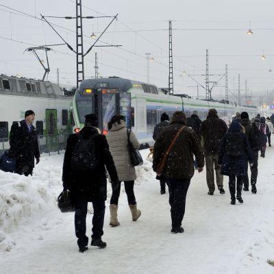 Passagerare går på en snöig perrong mot väntande tåg.