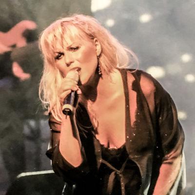 Josefin Nilsson en kvinna med blont hår och svarta kläder står på en scen och sjunger i en mikrofon, i bakgrunden syns en gitarrist.