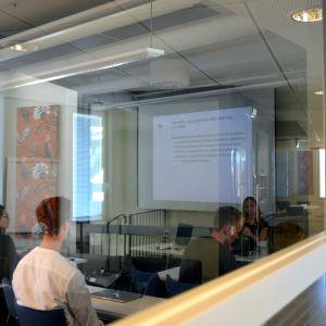 Studerande sitter i föreläsningssal. Fotat utifrån och bakifrån.