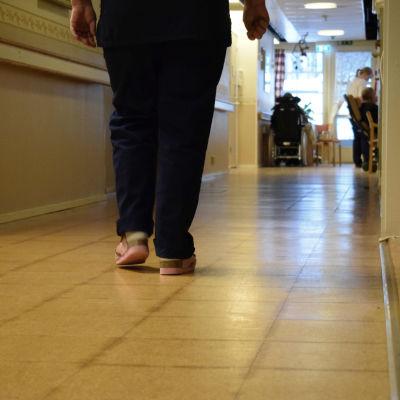 Två ben, en person som går i en korridor vid ett äldreboende.