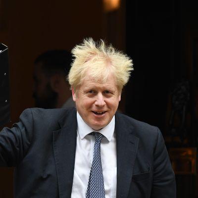 En leende Boris Johnsson viftar med men mapp i höger hand