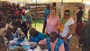 Maria Immonen Afrikassa pakolaisleirillä telttakatoksessa seuraamassa pakolaisten rekisteriöintiä