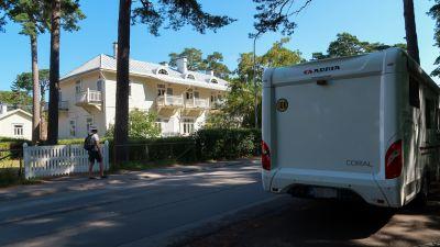Bild av husbil som är parkerad längs med vägen. På andra sidan vägen står ett hus.