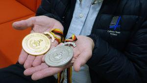 En man håller i två medaljer. Den ena är i guld och den andra i silver. På jackan står det Culinary Team Finland.