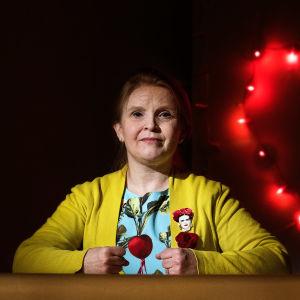 Jenni-Juulia Wallinheimo-Heimonen istuu pöydän takana kädet nyrkissä pöydän päällä. Tummassa taustassa vasemmalla puolella valonauhasta muodostuva sydän.