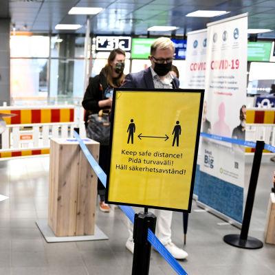 """""""Håll säkerhetsavstånd"""" står det på en skylt på Helsingfors-Vanda flygplats."""