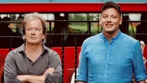 Kjell Westö med armarna i kors med småbutter min bredvid en glad Kqaj Korkea-aho i London. Röd buss i bakgrunden.