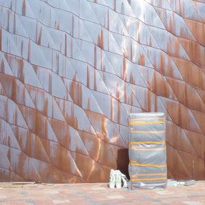Byggmaterial mot en vägg belagd med koppar.