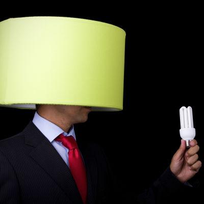 En man har en lampskärm på sitt huvud och håller i en lampa i sin hand som han håller framför skärmen.