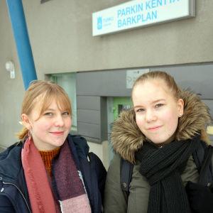 Eva Lohikoski och Mirjam Lillhannus, två flickor i vinterjackor framför ingången till Barkplan.
