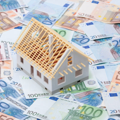 En husmodell står på en stor mängd sedlar.
