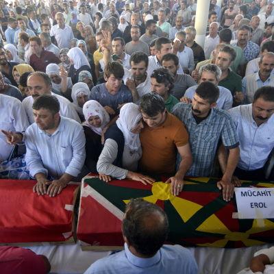 Släkt och vänner sörjer dem som dödades i en explosion i gränsstaden Suruc i Turkiet.