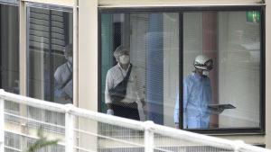 Poliser och räddningspersonal promenerar inne i den drabbade institutionens korridor efter massmordet .