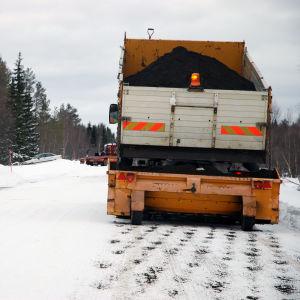 En lastbil sandar en väg.