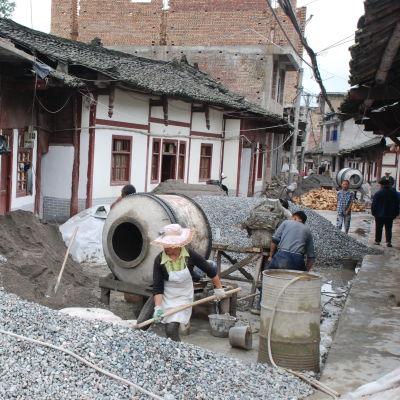 Grushögar, betongblandare och människor med spadar på en uppriven gata.
