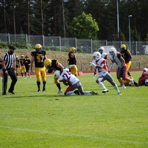 En spelare tacklar en annan genom att greppa tag om benen.
