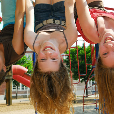 tre långhåriga flickor hänger skrattande upp och ner i en klätterställning