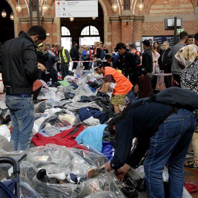 Rautatieaseman lattialle koottuja vaatteita tutkivia ihmisiä.