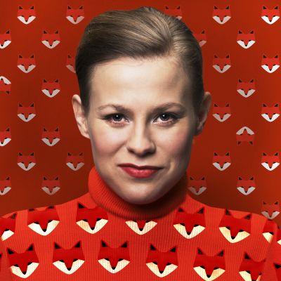 Kuvassa näyttelijä Emmi Parviainen punaisessa kettukuvioisessa paidassa, taustalla sama punainen kettukuviollinen tapetti.