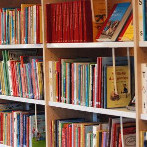 Barnböcker i en bokhylla på ett bibliotek.