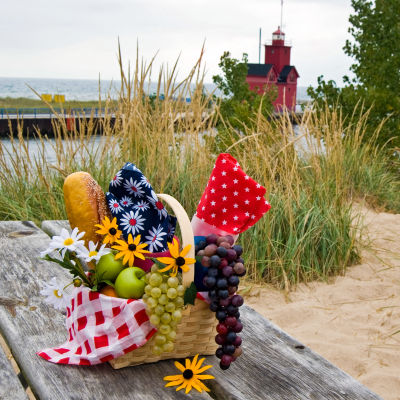 Ett slitet träbord med en picnickorg på en strandäng. I bakgrunden syns havet.