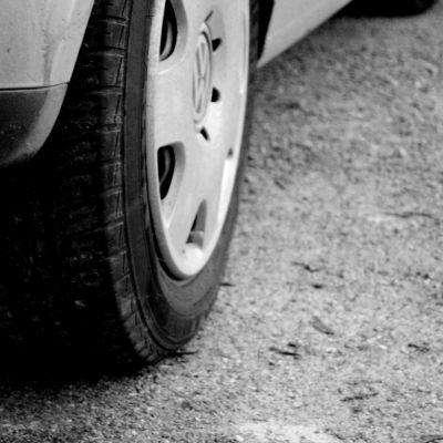 En bil parkerad, ena hjulet syns på bild.