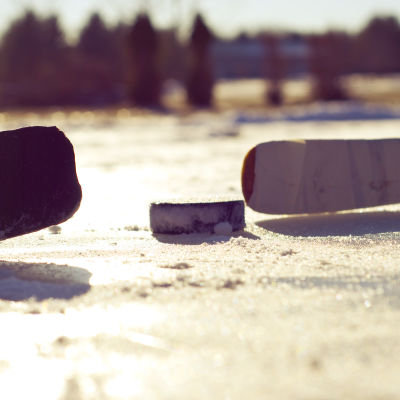Två hockeyklubbor och en puck i solnedgång