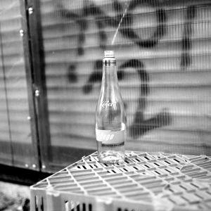 Christian löysi kadulle hylätyn pullon ja otti lomokameralla kuvan.