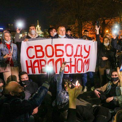 Demonstranter samlas kringen ett plaket med texten Frihet för Navalnyj på ryska.