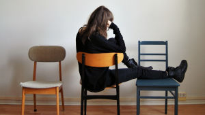nainen istuu tuolilla selin jalat toisella tuolilla