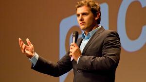 nuori mies puhuu mikrofoniin käsi ojennettuna