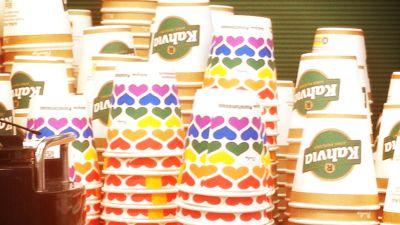 Vanliga reklamtryckta engångskaffemuggar och muggar med regnbågsmönster i staplar.