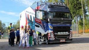 Barn framför den stora lastbilen