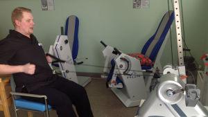Fysioterapeut Henri Alm visar roddrörelsen som ger de äldre styrka i nypor och armar.