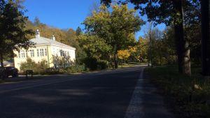 Vägen i Fiskars bruk, det gamla Wärdshuset till vänster, höst och sol.
